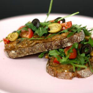 Chlebíček s lilkovou tapenádou, cherry rajčaty, rukolou a olivami